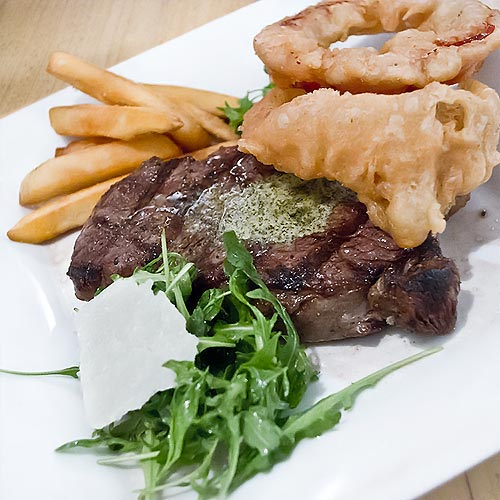 The Herd Steak Restaurant sirloin steak, twice cooked chunky chips, thick cut onion ring, herd thick cut pepper ring, and rocket and parmesan salad